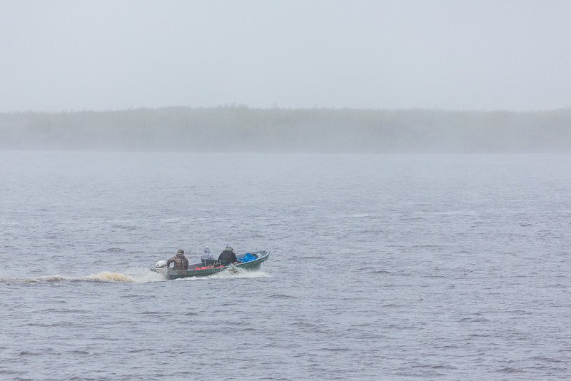 Morning fog on the Moose River at Moosonee. Open canoe coming up the river.