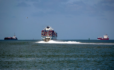 The Cosco Aukland container ship leaves the ship channel followed by a fast tug boat.