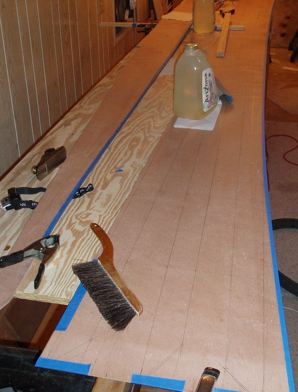 The 1st edge of the 4th panel has been cut, trimmed and taped. The 2nd modification to the stock plans can now be seen. The top edge of the bow has been raised 2 1/4 inches tapering back about 4 feet, this in theory is to help rise over waves instead of through them.
