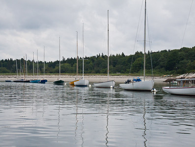 Photograph of Small Point One Design (SPOD) sailboats at anchor in mooring field in The Branch, Small Point Harbor, PHippsburg, Maine with nice reflections and Bailey Beach in the background, image, photography, Vacationland, sailing race, Small Point Sailing Club