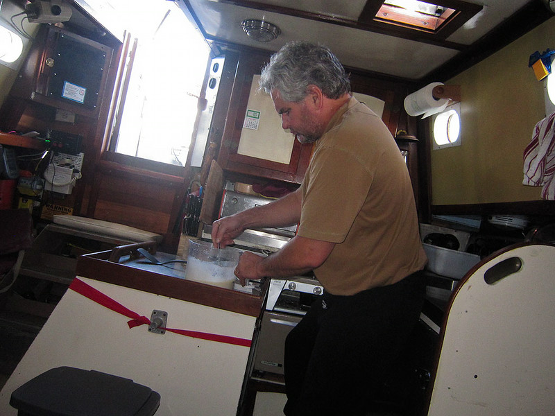 ps-2703 It's just before 8AM Tuesday morning, chef Scott whipping up some pancakes.  The picture is level, it's the boat that's crooked.  For most of the trip we had beam seas rolling us and Tues was the day of big swells from the south which makes it a challenge to cook without making a mess of the galley.