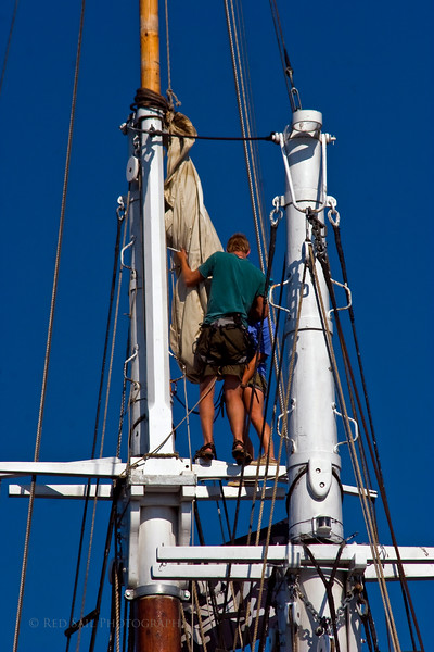 """Two crew members working aloft on the vessel Nathaniel Bowditch. The Nathaniel Bowditch was built as a racing yacht in 1922 in East Boothbay, Maine. This 82' windjammer accomodates 24 guests. More info at  <a href=""""http://www.windjammervacation.com"""">http://www.windjammervacation.com</a>."""