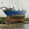 Guanahani Aground in Jekyll Creek. During gale force winds of an extended NorthEaster, a sail unfurled and dragged the vessel out of the Golden Isles Marina Anchorage through St. Simons Sound, down Jekyll Island, and into Jekyll Creek where she finally grounded on the Jekyll Creek Jetty behind the front range marker even with her anchor in tow. Low Tide.  Front of keel resting on rock. Rudder mount on rock. Rest of keel clear. Ungrounding by TowBoatUS Brunswick. Image 05-22-09