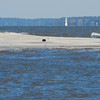 Sunken sailboat at high tide offshore Altamaha Sound, Georgia. TowBoatUS Brunswick rescued the man on board during the night that the vessel grounded further offshore. Vessel sank within minutes of man's extraction. Sapelo Island and Sapelo Lighthouse in background.