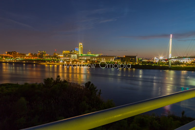 Downtown Omaha at night from Bob Kerrey Pedestrian Bridge. Douglas street bridge at extreme left. Missouri river in foreground