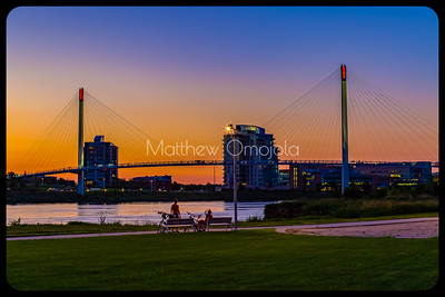 Riverfront Place Omaha  and Bob Kerrey Bridge after sunset. Bikers resting on bench in Tom Hanafan plaza Iowa