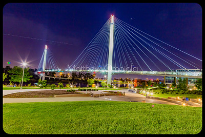 Bob Kerrey Pedestrian Bridge at night. Aircraft light trail on the left in the sky.