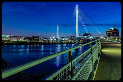Bob Kerrey Pedestrian Bridge at night. Bike light trail on bridge. Shimmering Missouri river to the left.