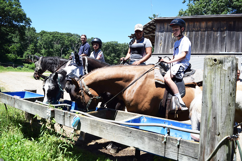 . Riders at Bobby s Ranch in Westford let their rented mounts hydrate before setting off. From left are Ken Mierz, Cameron Mierz, Gia Zermani and Connor Mierz. The Mierzes are from Westford; Zermani is from Lynnfield. SUN / SCOTT SHURTLEFF