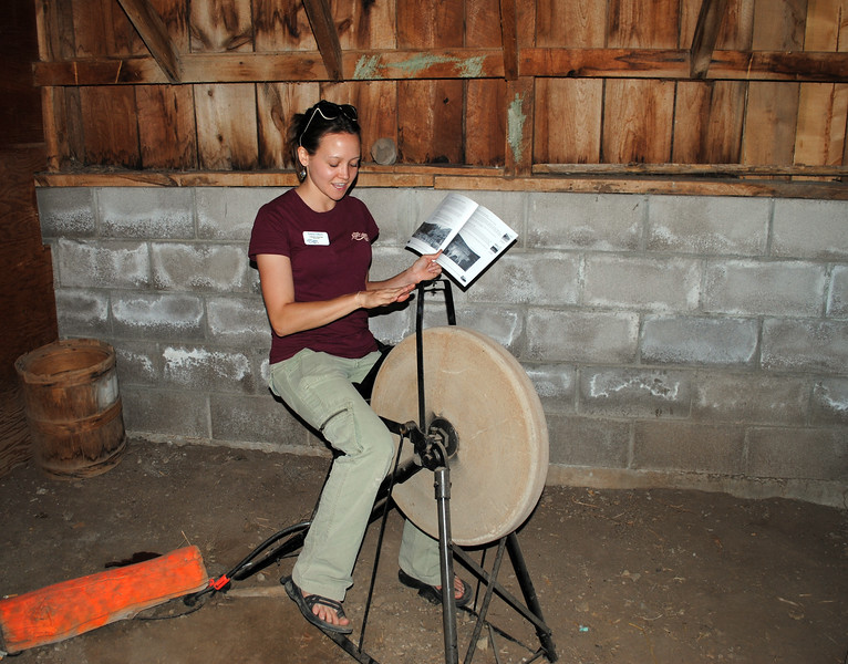 Emily Olivo, an educator with Fort Collins Natural Areas, demonstrates how this wheel was once used to sharpen tools. (Pamela Johnson / Loveland Reporter-Herald)