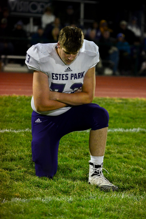 . Jacub Steckline takes a knee for an injured teammate during the last game of his high school career. The Bobcats lost 47-3 to the Highland Huskies in Ault, Colo., on Oct. 25.