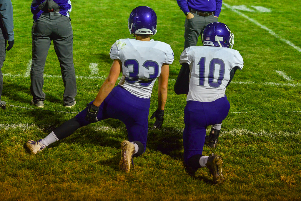 . Dennis Campos, left, and Tucker Johnson take a knee on the sidelines followin an injury of their teammate.  The Bobcats lost 47-3 to the Highland Huskies in Ault, Colo., on Oct. 25.