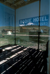 The window in the Bodie Hotel (renamed from Wheaton and Hollis Hotel reflects the buildings, truck and gas pumps across the street.