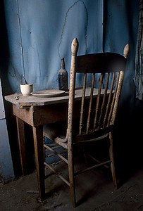 Table and chair in small bedroom near the assay office.