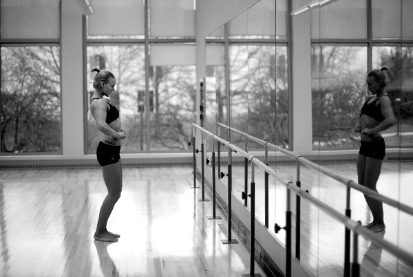 Kaylee practices her posing in an empty dance room in her gym at Indiana State University.