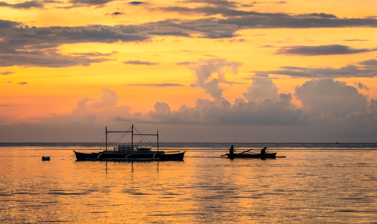 Local fishermen glide past a moored boat on their way to fishing grounds at Anda on the island of Bohol in the Philippines