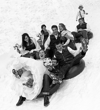 Happy Newlyweds sledding with Wedding party