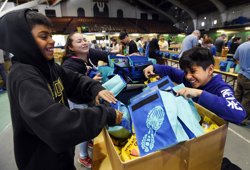 . Kevin Delgado, left, and Jose Bautista, both 12, put chips in lunch bags for runners in Monday\'s Bolder Boulder. Members of the University of Colorado men\'s club lacrosse team  among others, put down the Folsom Field floor and volunteers packed lunches 55,000 in Balch Field House on Saturday. For more photos and a video, go to www.dailycamera.com.  Cliff Grassmick  Staff Photographer May 27, 2017