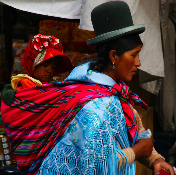 """A Bolivian lady carries her baby on her back at a local market - La Paz, Bolivia.  This is a travel photo from La Paz, Bolivia. <a href=""""http://nomadicsamuel.com"""">http://nomadicsamuel.com</a>"""