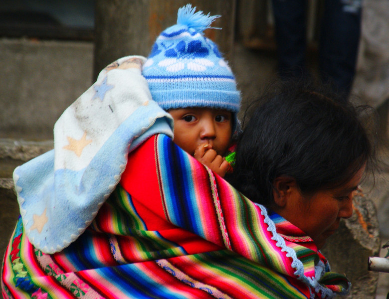 "Baby on back of Mom as she strolls around the market - La Paz, Bolivia. <a href=""http://nomadicsamuel.com"">http://nomadicsamuel.com</a>"