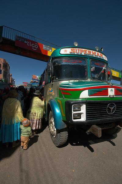 Locals load onto a colourful bus in El Alto.