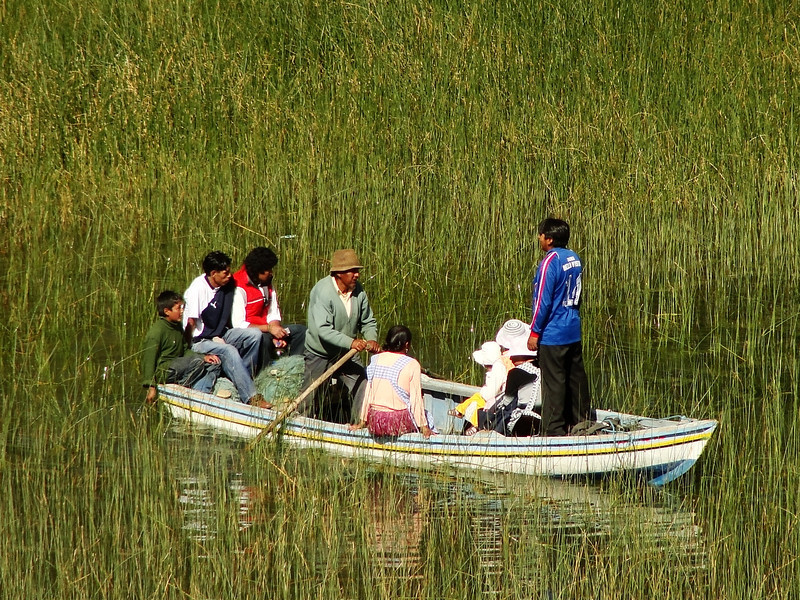 Today's daily travel photo is an authentic scene of a Bolivian family crossing a section of Lake Titicaca by rowboat near Copacabana, Bolivia.