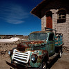 A rusted truck sits in front of a salt home in the town of Colchani.