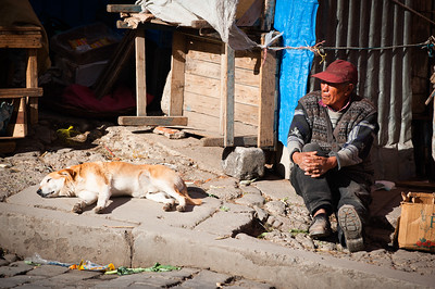 A Bolivian man sits on the floor in the sunshine, La Paz, Bolivia, South America