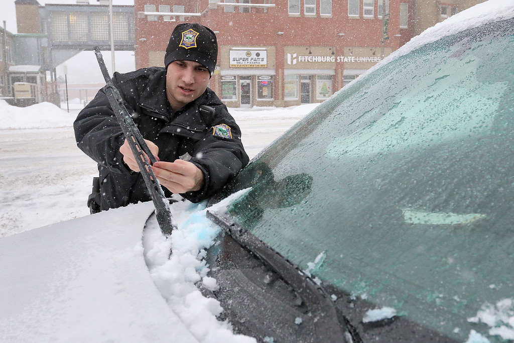 . On duty Fitchburg Officer Nathan Lamkin took some time to clean off the windshield of his cruiser during Thursday\'s storm. SENTINEL & ENTERPRISE/JOHN LOVE