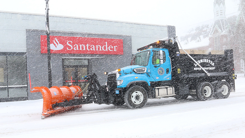. A plow plows the street in fron of Santander bank in Leominster during Thursday\'s storm. SENTINEL & ENTERPRISE/JOHN LOVE