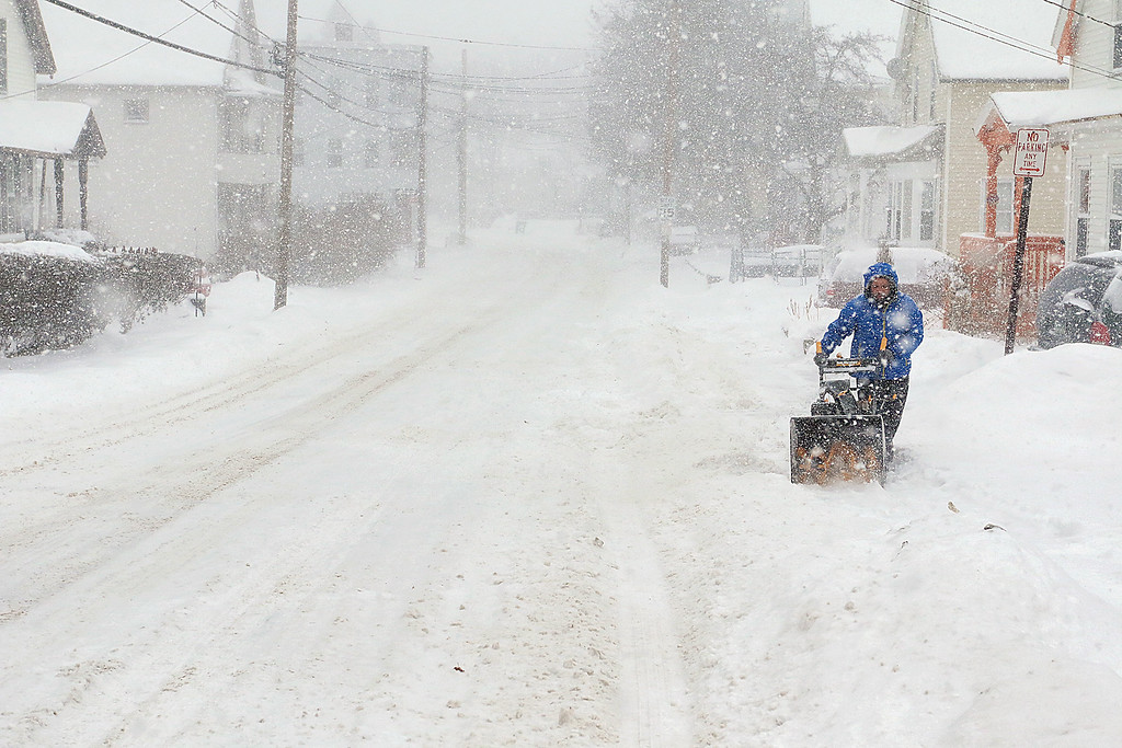 . A resident on Rollstone Street snow plows the sidewalk in front of his house during Thursday\'s storm. SENTINEL & ENTERPRISE/JOHN LOVE