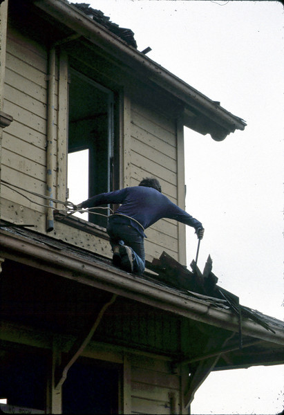 """""""Charlie"""" removes old shingles from roof, 6/1982. acc2005.001.0232"""