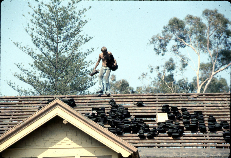 Fireman assists in roof-removal effort, 6/1982. acc2005.001.0233