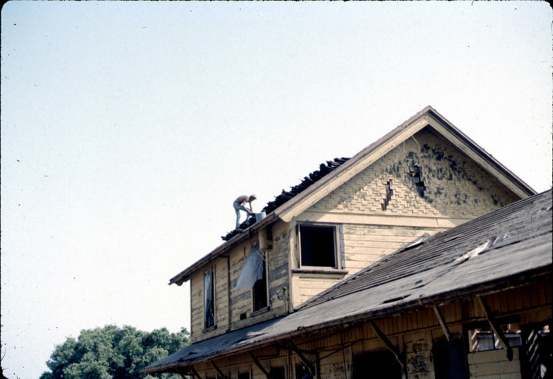 Fireman assists in roof-removal effort, 6/1982. acc2005.001.0235