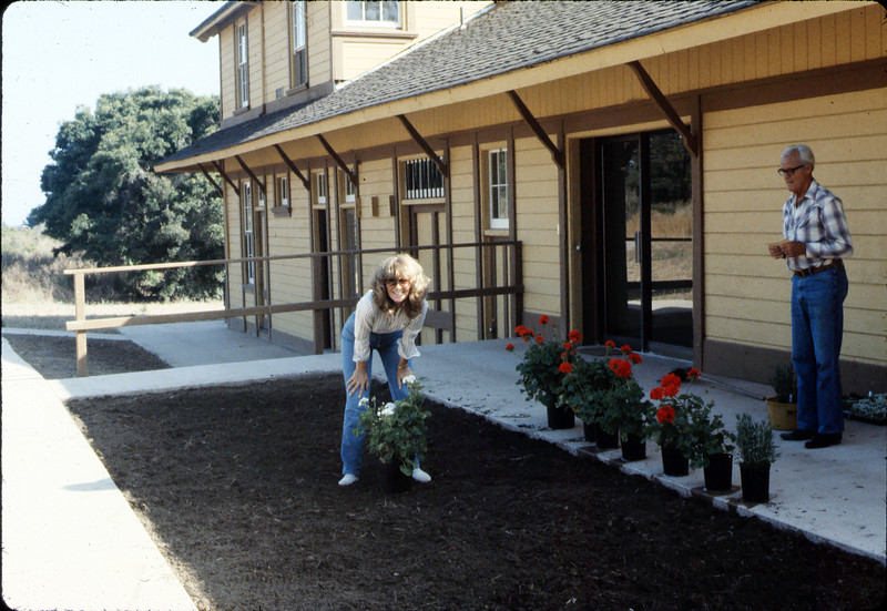 Phyllis Olsen and George Adams planting geraniums in planter in front of Chamber of Commerce office, 7/1983. acc2005.001.0377
