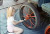 Chaska Conrow paints baggage cart wheels, Work Day, 3/1988. acc2005.001.0907