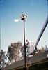 Bill Battisone, OK Tree Service, installs ladder on train-order pole, Work Day, 4/9/1988. acc2005.001.0919