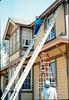 M&M Construction installs new redwood gutters, 5/1988. acc2005.001.0977