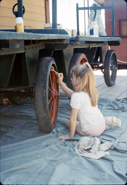 Chaska Conrow paints baggage cart wheels, Work Day, 3/1988. acc2005.001.0912