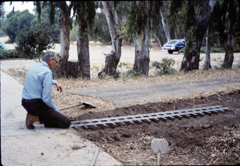 Gene Allen prepares ground for miniature-railroad crossing at museum's entry sidewalk, 5/1987. acc2005.001.0797