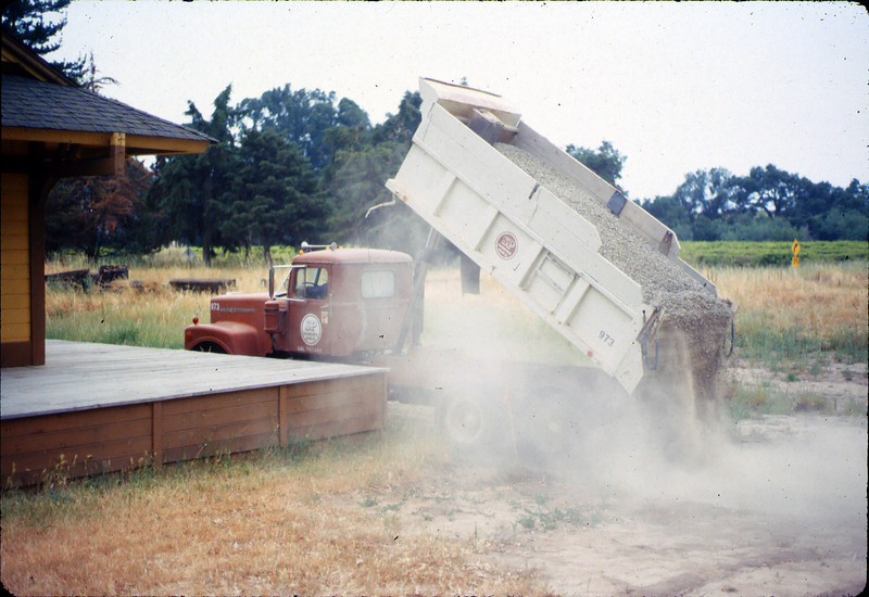 Standard-gauge track laying; pouring ballast rock, 1985. acc2005.001.0530