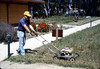 Gene Boswell mows weeds around grounds, Spring 1986 (sic) acc2005.001.0680