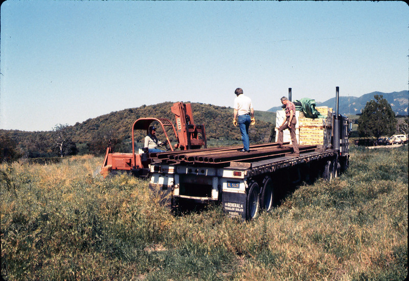 Laying of the standard-gauge track (John Lebeck and Gene Allen on truck; Ed Lebeck operating forklift), 4/2/1985 acc2005.001.0475
