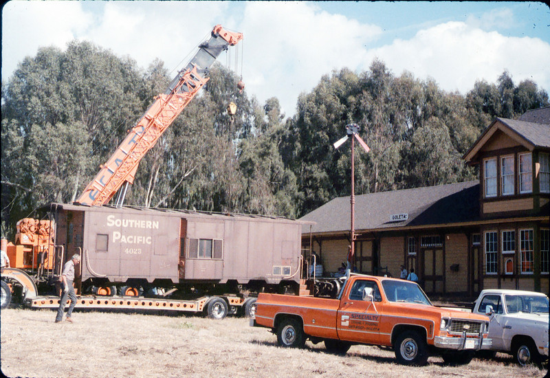 Crane will soon move caboose body onto the awaiting trucks, 9/25/1986 acc2005.001.0636