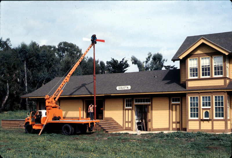 Bill Everett watches as train-order pole is attached to its foundation, 10/1983. acc2005.001.0430