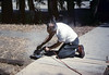 Ralph Moore cuts the sidewalk for the miniature-railroad crossing, 6/1987. acc2005.001.0804