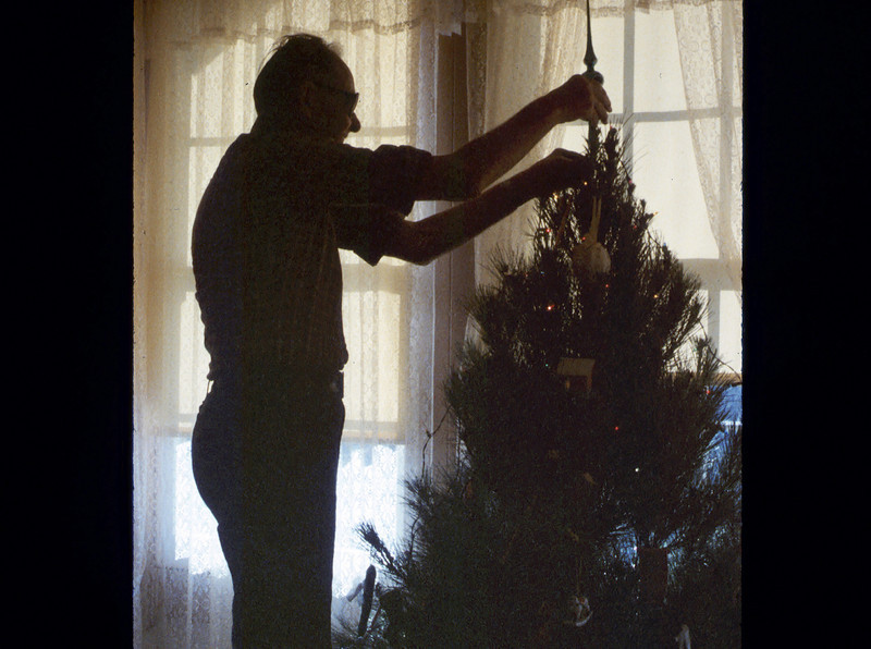 Gene Allen affixes the crowning ornament on the museum Christmas tree, 12/1986. acc2005.001.0654