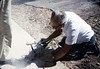 Ralph Moore cuts the sidewalk for the miniature-railroad crossing, 6/1987. acc2005.001.0808