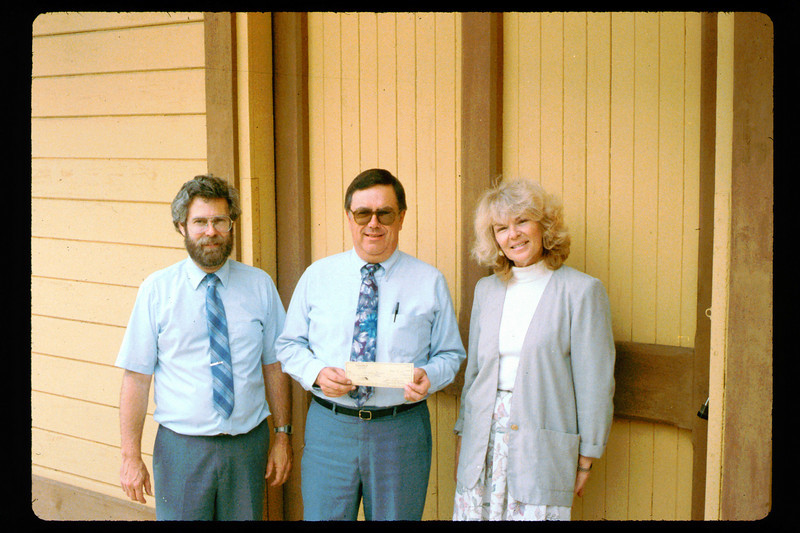 Bruce Schumikowski presents check from Goleta Lions (Santa Barbara News-Press?) to Gary Coombs and Phyllis Olsen, 1991. acc2005.001.1506
