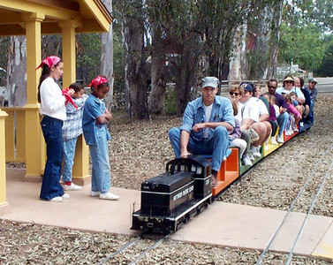 """Miniature-train passes the entrance to the museum grounds.  If this photo is your favorite, click on the """"ADD COMMENT"""" button at the lower left to tell us why you like this particular photo. Please include your name and contact information (Parental approval is required if you are under age 18)."""